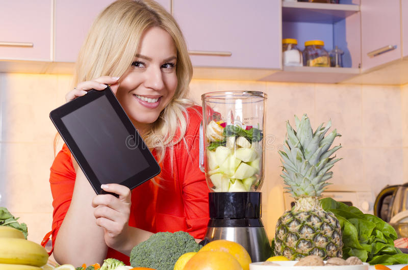 Femme heureuse jugeant le comprimé à côté d'un presse-fruits plein du fruit image stock
