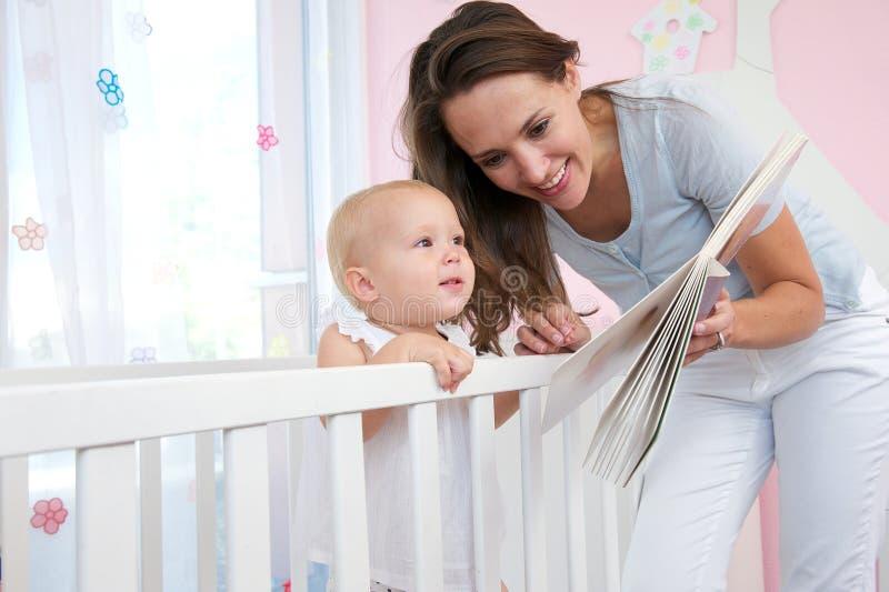 Femme heureuse lisant un livre à un bébé mignon image stock