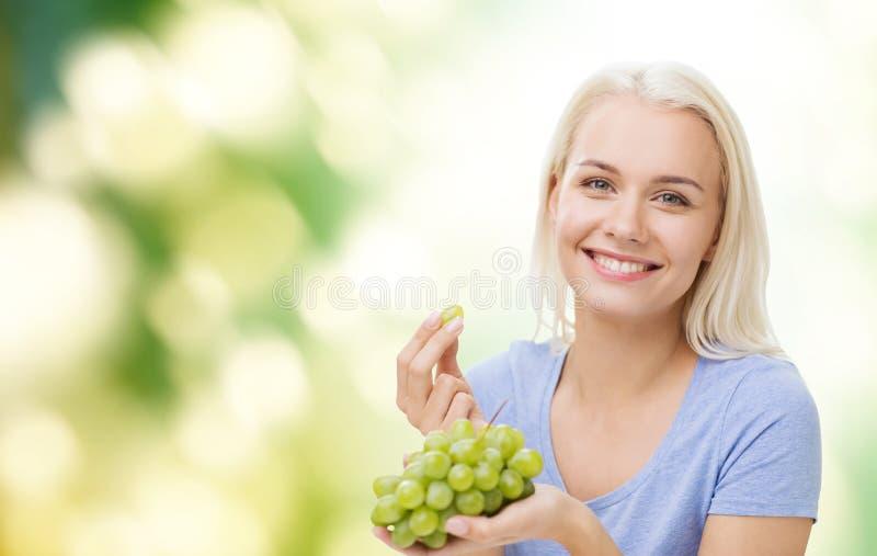 Femme heureuse mangeant des raisins images stock