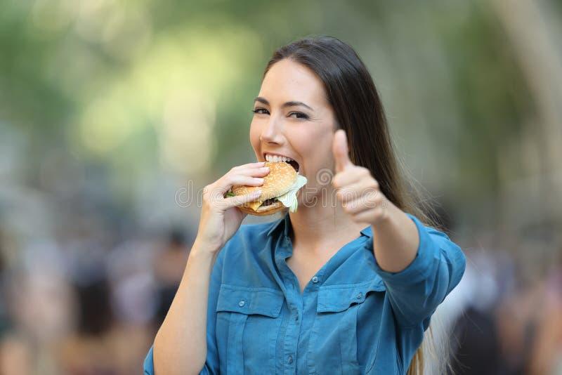 Femme heureuse mangeant l'hamburger faisant des gestes le pouce  photos stock