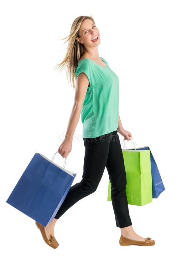 Femme heureuse marchant avec des sacs à provisions photo libre de droits