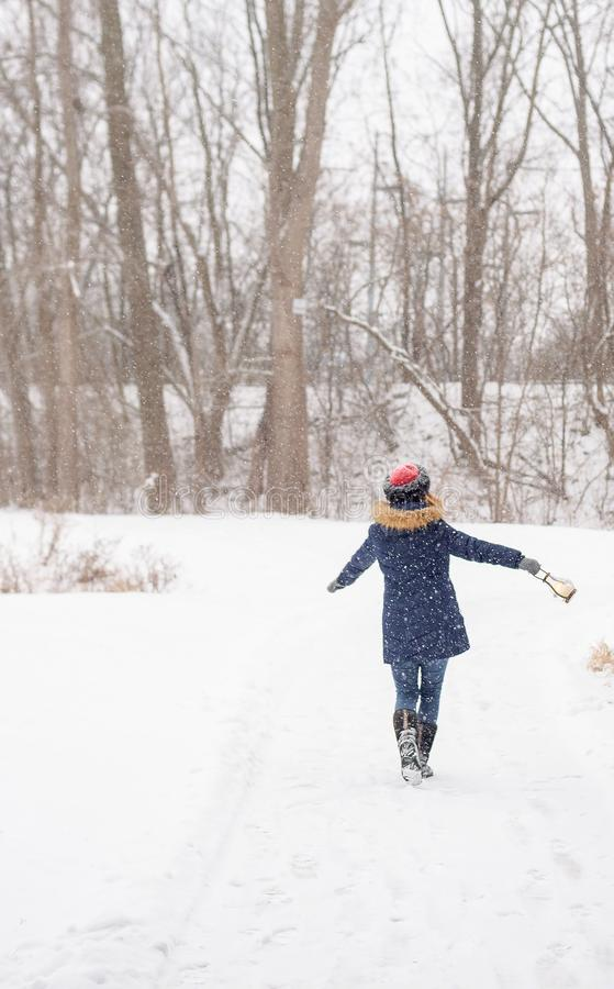 Femme heureuse marchant et dansant en bois tandis que la neige fraîche tombe photos stock