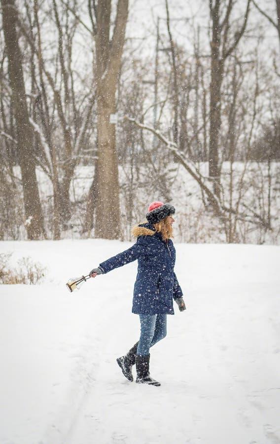 Femme heureuse marchant et dansant en bois tandis que la neige fraîche tombe photographie stock