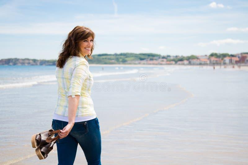 Femme heureuse marchant le long du bord de la mer photo stock