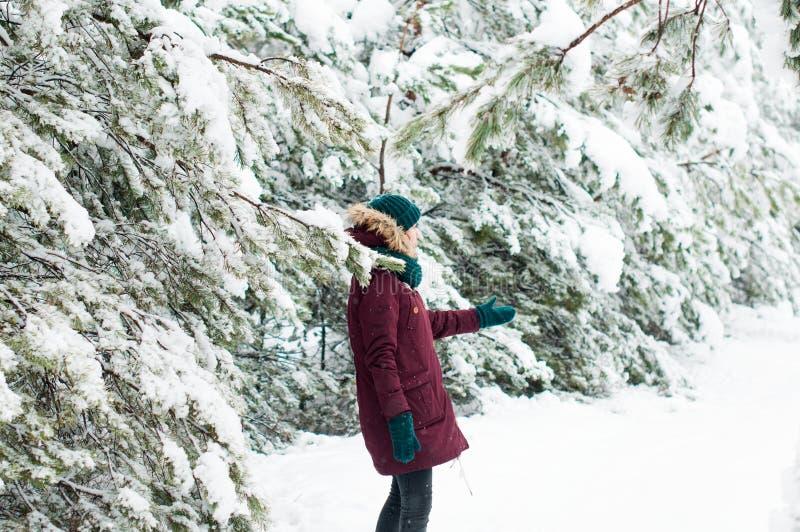 Femme heureuse marchant par une forêt neigeuse image stock