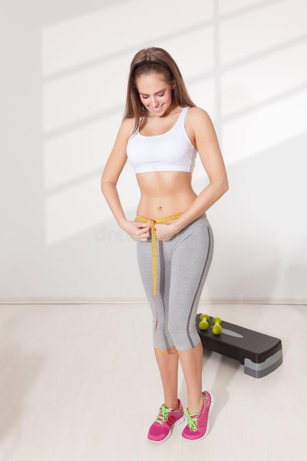 Femme heureuse mesurant sa taille images libres de droits