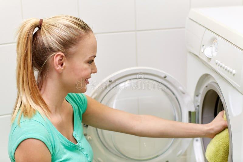 Femme heureuse mettant la blanchisserie dans le joint à la maison image libre de droits