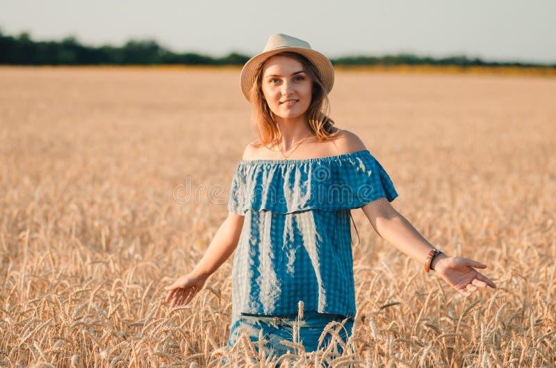 Femme heureuse mignonne dans le chapeau sur le champ de blé d'été photographie stock