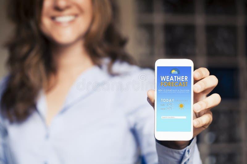 Femme heureuse montrant un téléphone portable avec des prévisions météorologiques dans photo libre de droits