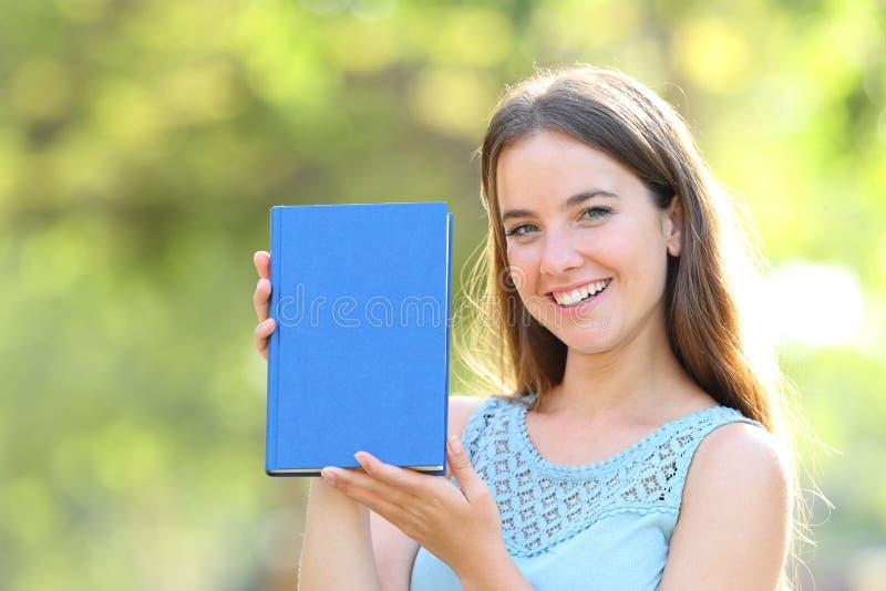 Femme heureuse montrant une couverture de livre vide images stock