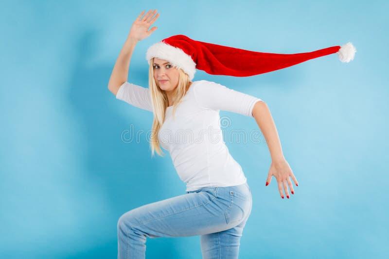 Femme heureuse portant le fonctionnement de chapeau de Santa Claus images stock