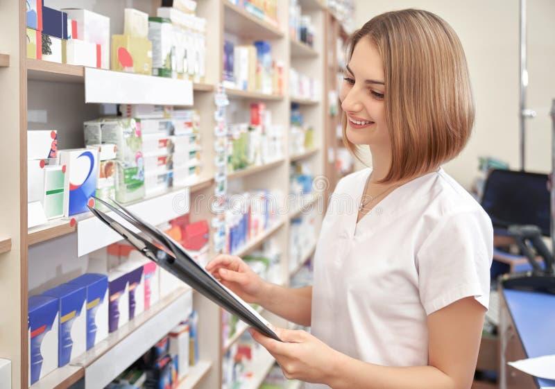 Femme heureuse posant tout en travaillant dans la pharmacie photo libre de droits