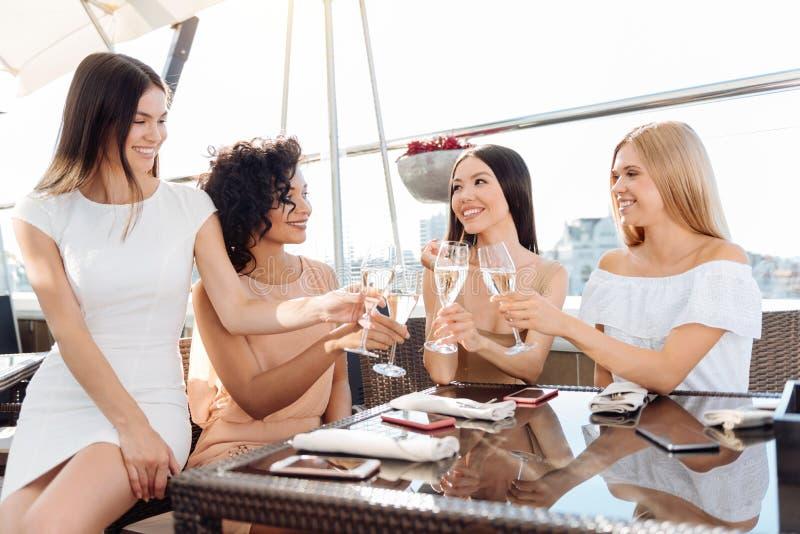 Femme heureuse positive faisant tinter leurs verres image libre de droits