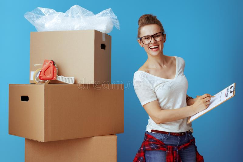 Femme heureuse près de liste de contrôle mobile de repérage de boîte en carton sur le bleu photo stock
