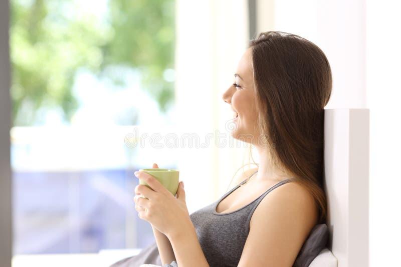 Femme heureuse prenant le petit déjeuner sur le lit image libre de droits