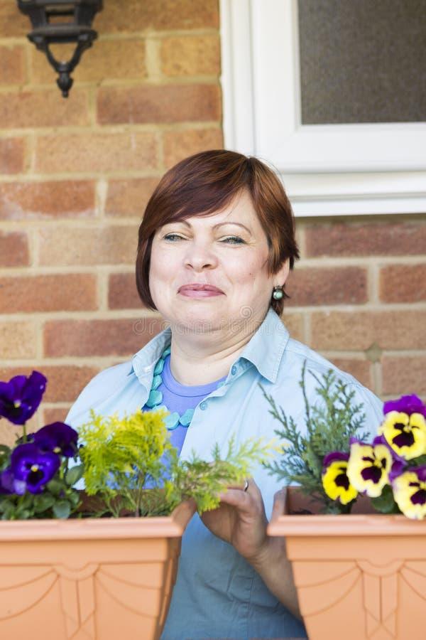 Femme heureuse prenant soin des fleurs dehors photographie stock