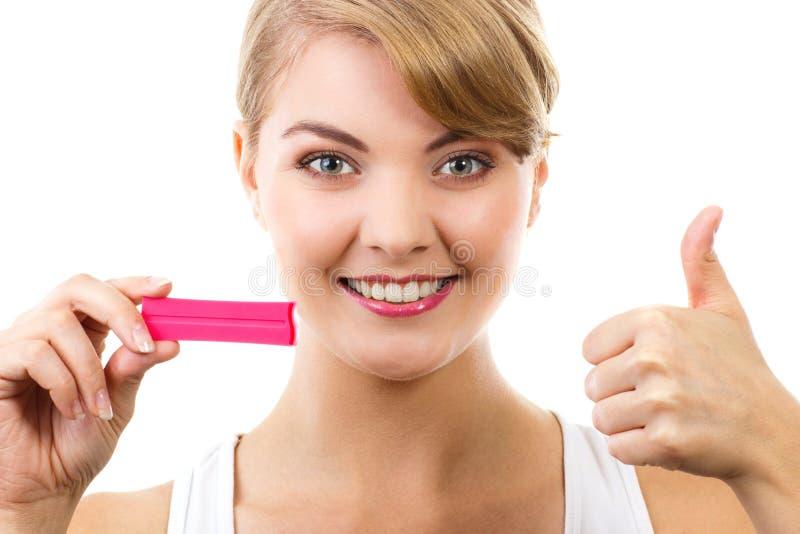Femme heureuse regardant l'essai de grossesse avec le résultat positif et montrant des pouces  photographie stock libre de droits