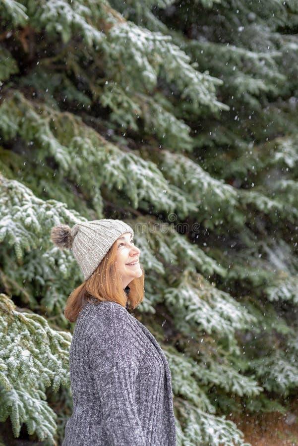 Femme heureuse regardant la chute de neige photo libre de droits