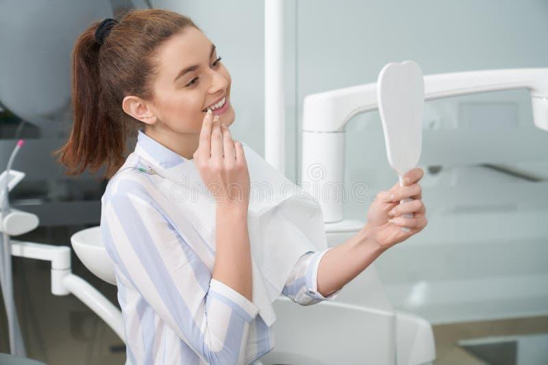 Femme heureuse regardant le miroir dans la clinique d'art dentaire photographie stock libre de droits