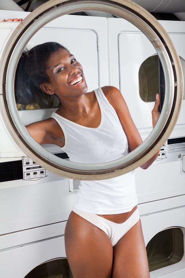 Femme heureuse regardant par la porte de machine à laver image libre de droits