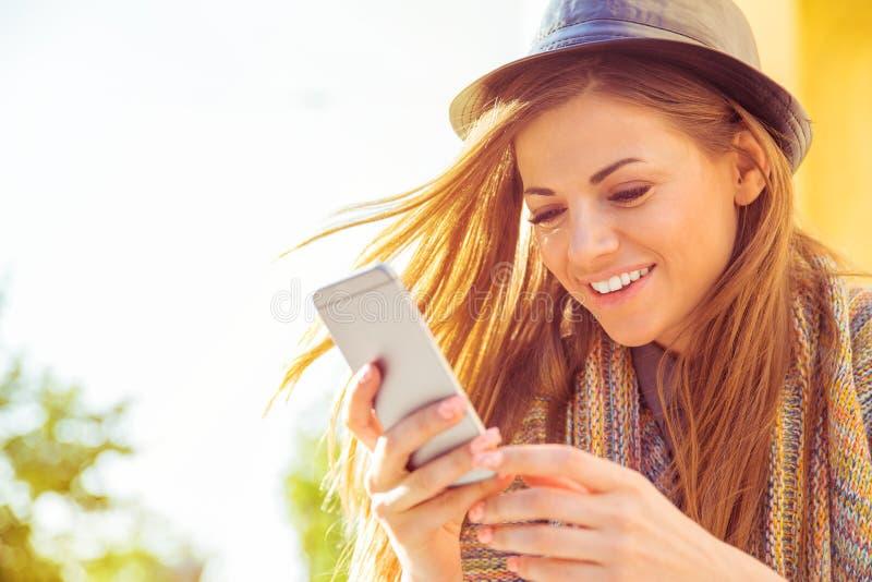 Femme heureuse reposant textoter dehors au téléphone intelligent dans la rue un jour ensoleillé d'automne photos stock