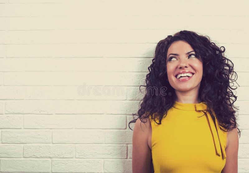 Femme heureuse riante, d'isolement sur le fond de mur de briques photos stock