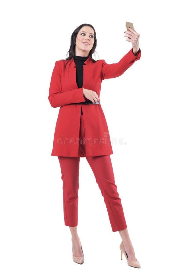 Femme heureuse sûre d'affaires tenant et prenant des photos de selfie avec le téléphone portable photo libre de droits