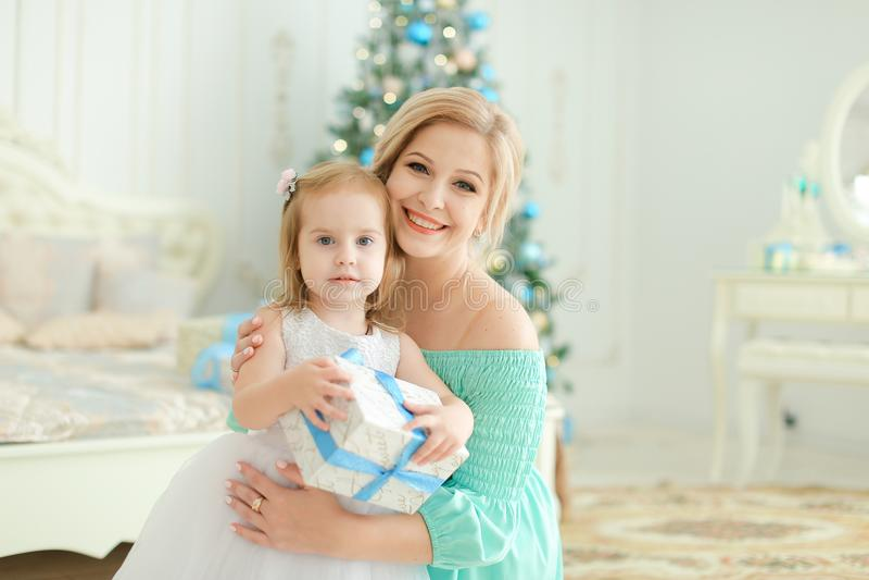 Femme heureuse s'asseyant avec la petite fille gardant le présent, arbre de Noël à l'arrière-plan photo libre de droits