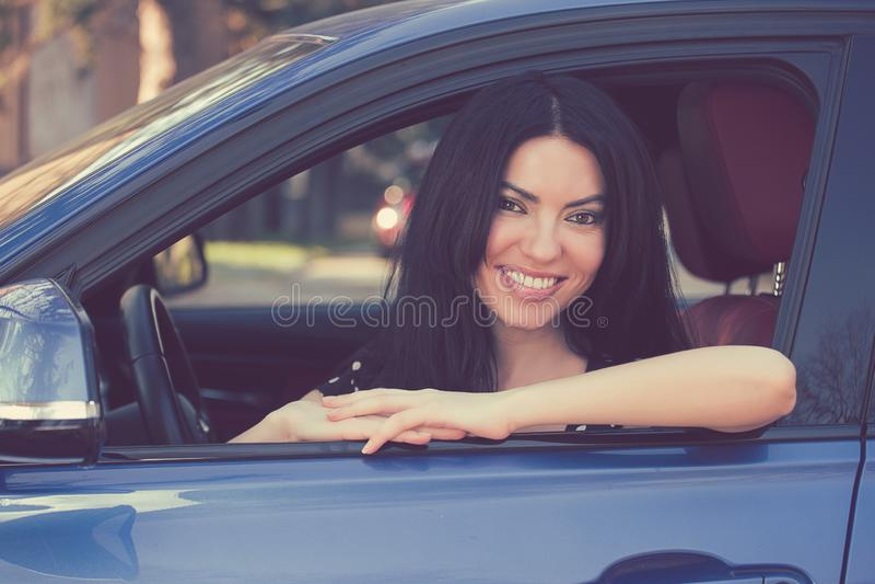 Femme heureuse s'asseyant dans une voiture moderne image stock
