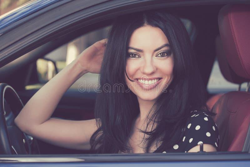 Femme heureuse s'asseyant dans une voiture moderne images stock