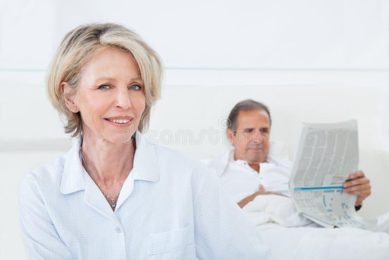 Femme heureuse s'asseyant en Front Of Man image libre de droits