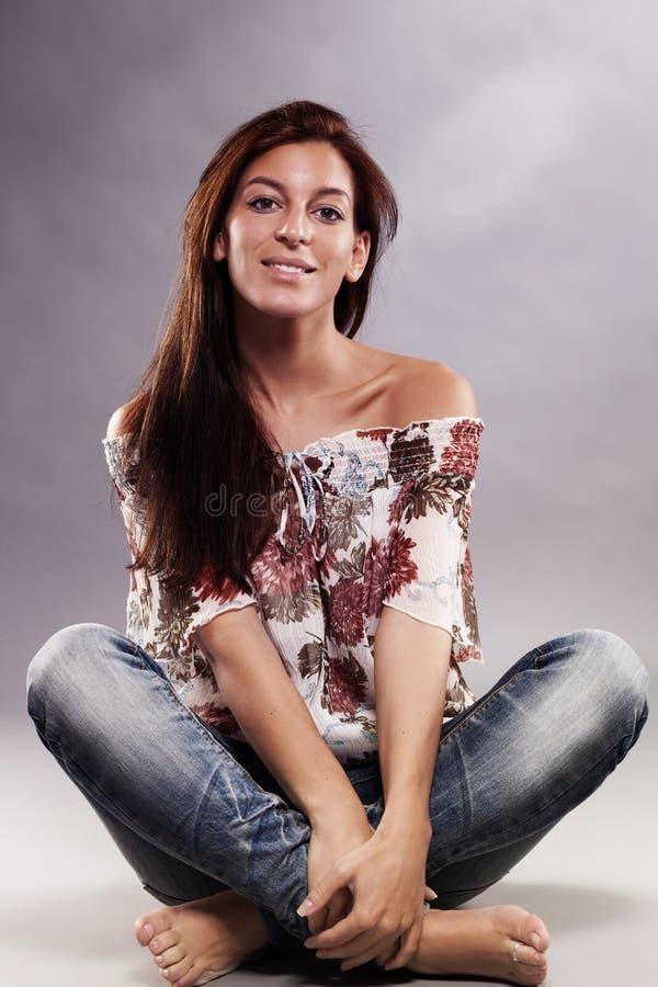 Femme heureuse s'asseyant sur l'étage photos libres de droits