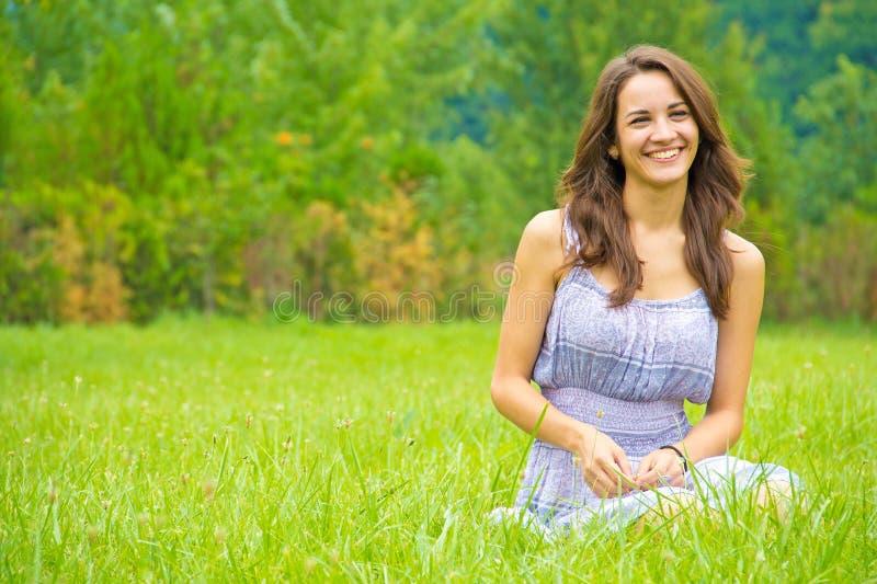 Femme heureuse s'asseyant sur l'herbe image libre de droits
