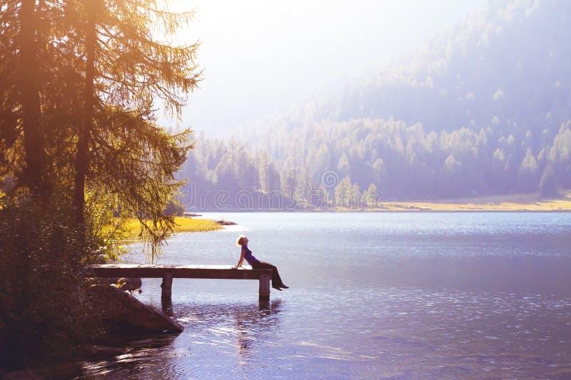 Femme heureuse s'asseyant sur le concept de pilier et de sourire, de bonheur ou d'inspiration photographie stock libre de droits
