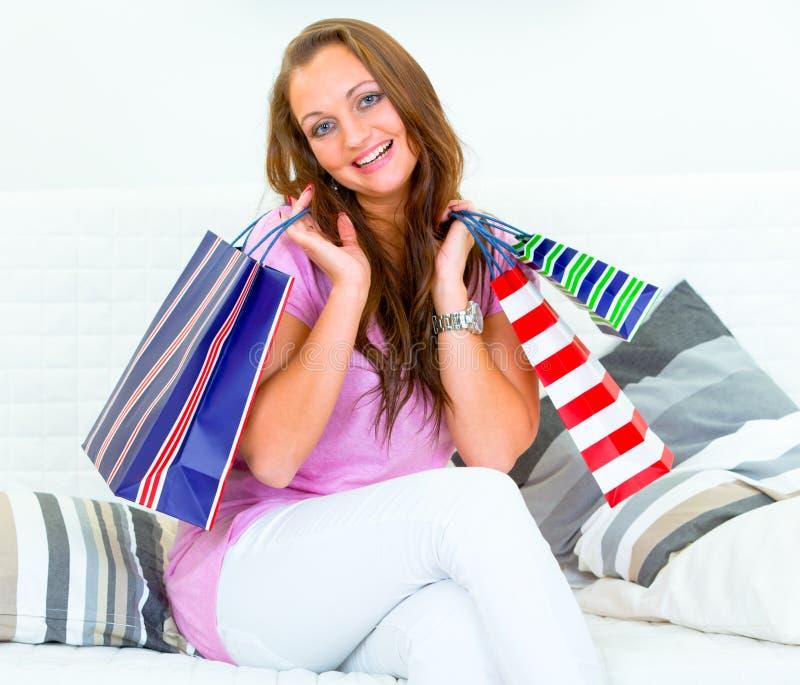 Femme heureuse s'asseyant sur le divan avec des sacs à provisions image stock