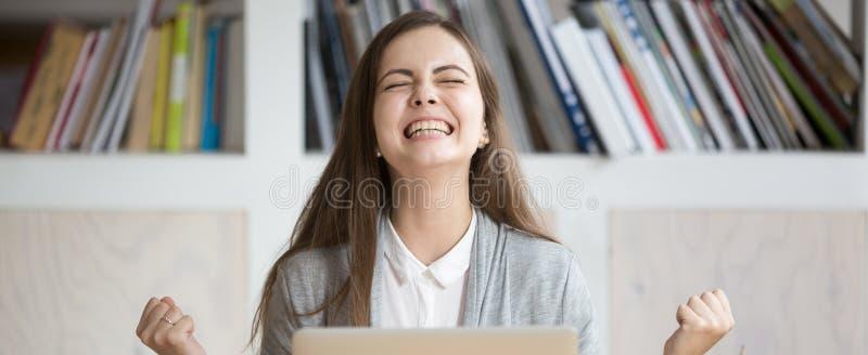 Femme heureuse s'asseyant sur le lieu de travail célébrant la grande opportunité au travail images libres de droits