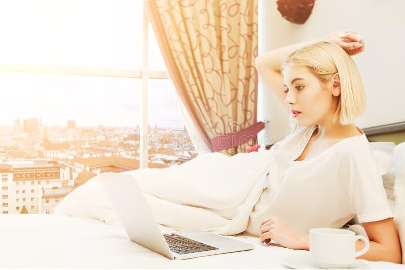 Femme heureuse s'asseyant sur le lit dans la chambre d'hôtel images stock