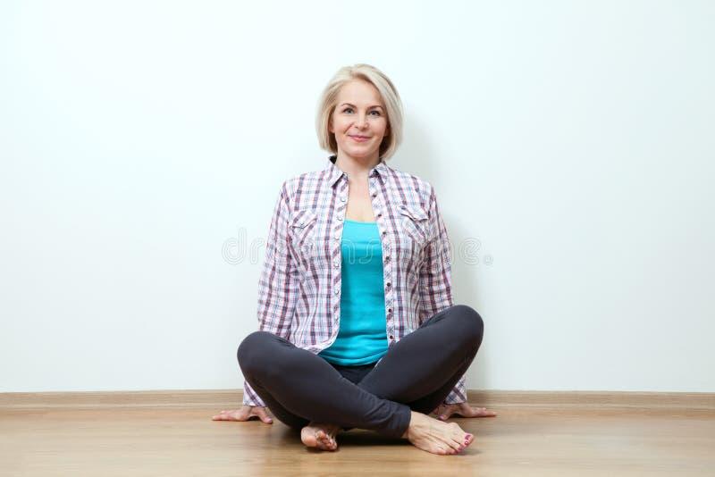 Femme heureuse s'asseyant sur le plancher avec les jambes croisées dans le studio photos stock