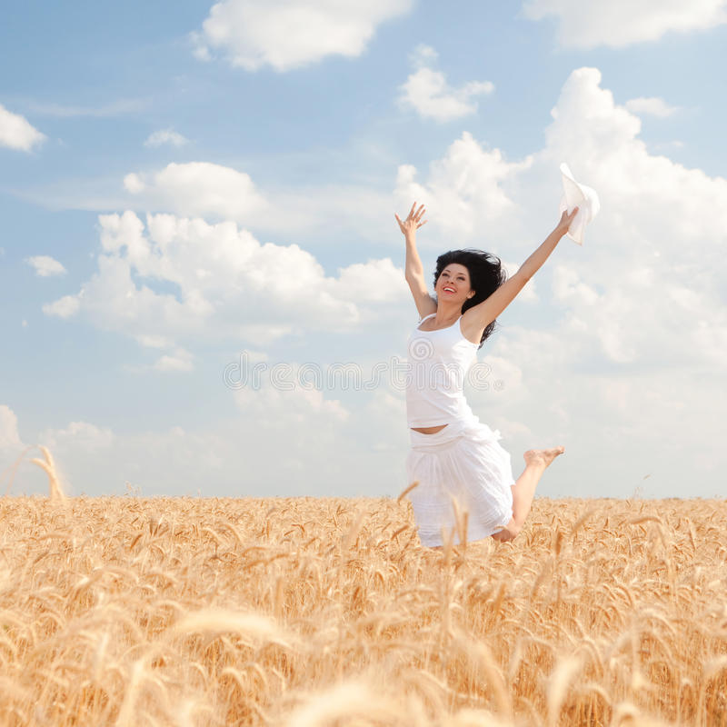 Femme heureuse sautant dans le blé photos stock