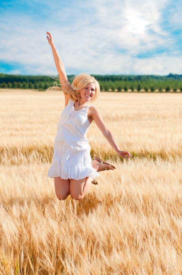 Femme heureuse sautant dans le blé d'or image stock
