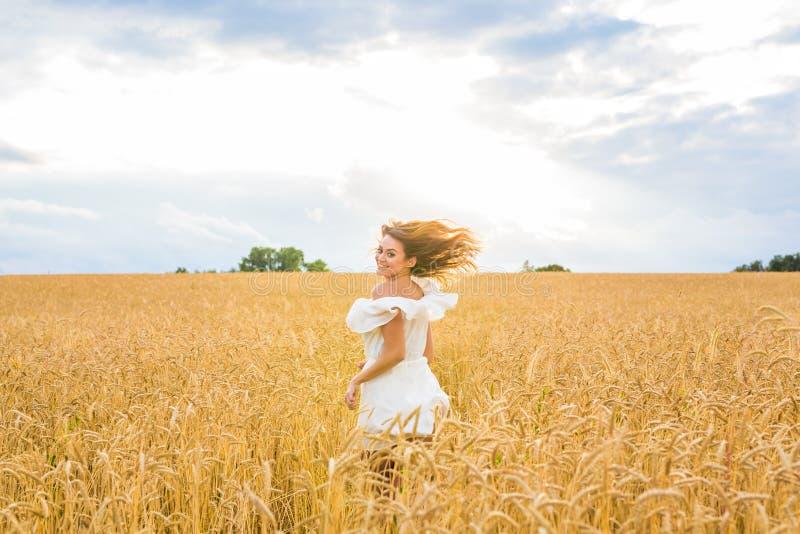 Femme heureuse sautant dans le blé d'or photos libres de droits
