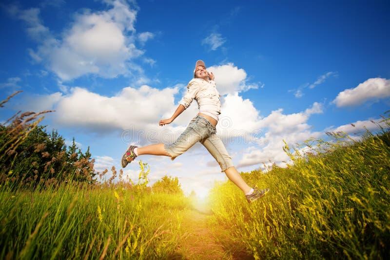 Femme heureuse sautant par-dessus le ciel bleu photo libre de droits