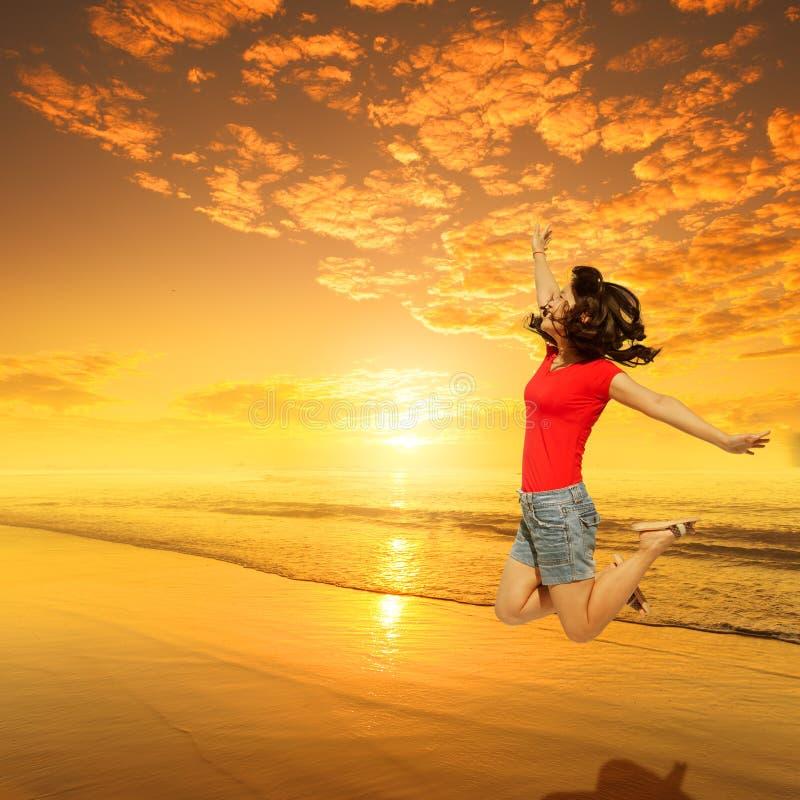 Femme heureuse sautant sur le coucher du soleil de plage sur le T-shirt rouge image libre de droits