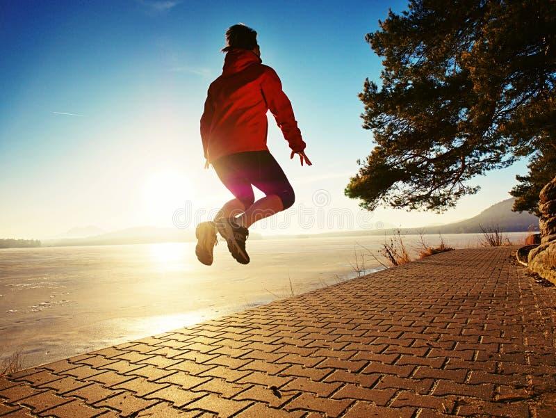 Femme heureuse sautant sur le rivage de lac, plage de chemin au coucher du soleil photographie stock