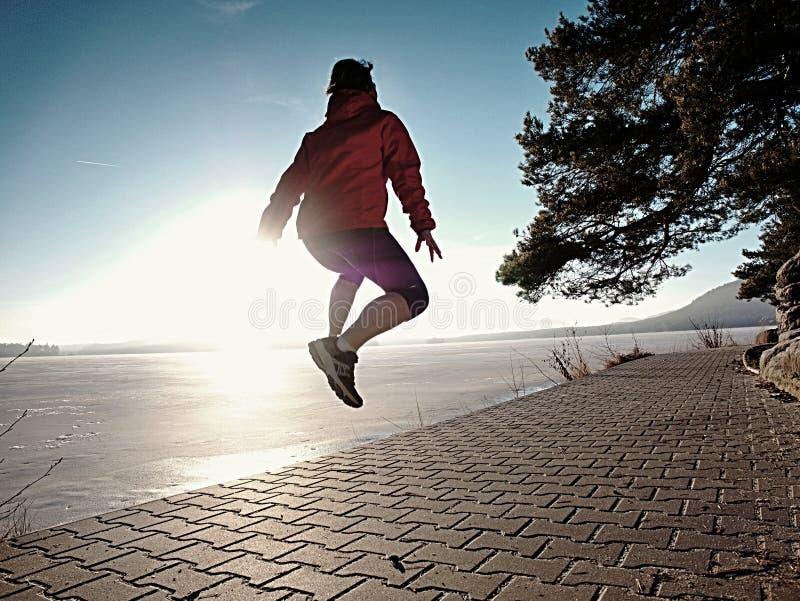 Femme heureuse sautant sur le rivage de lac, plage de chemin au coucher du soleil photos libres de droits