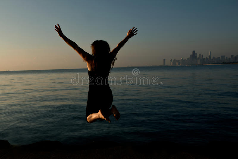 Femme heureuse sautant tout près le lac Michigan au lever de soleil photos libres de droits