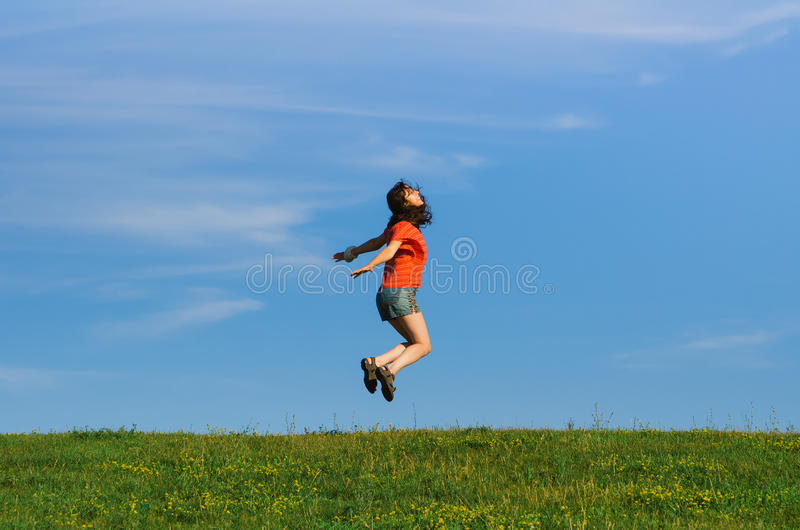 Femme heureuse sautante d'émotion sur des milieux d'herbe et de ciel image stock