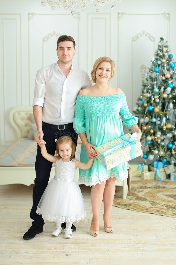 Femme heureuse se tenant avec la petite fille gardant le présent, arbre de Noël à l'arrière-plan images libres de droits