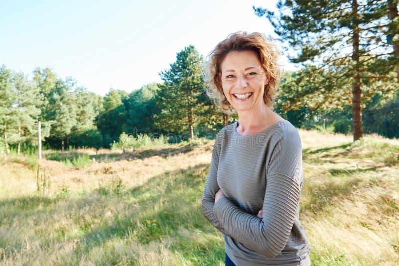 Femme heureuse se tenant dans la campagne avec des bras croisés images stock
