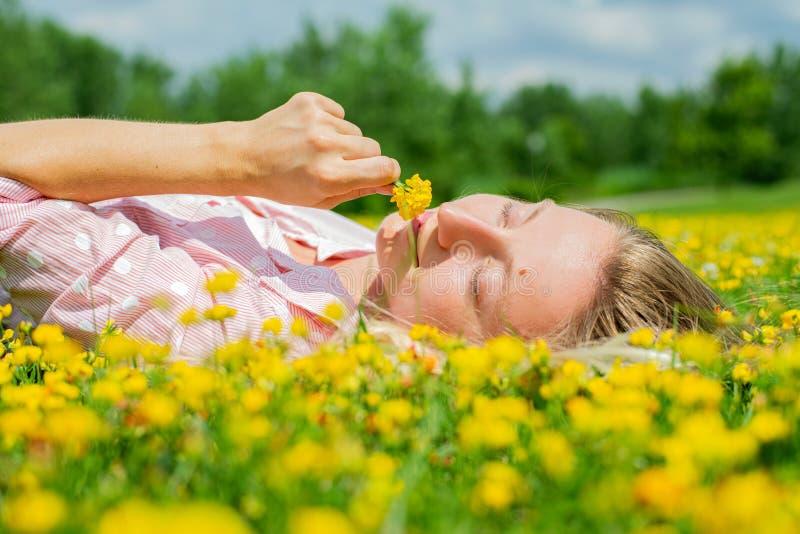 Femme heureuse se trouvant sur le champ dans l'herbe avec les fleurs jaunes dehors Appr?ciez la nature Allergie gratuite images libres de droits